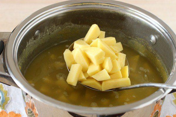 Нарезанный маленькими кусочками сырой картофель в большой ложке над кастрюлей с супом