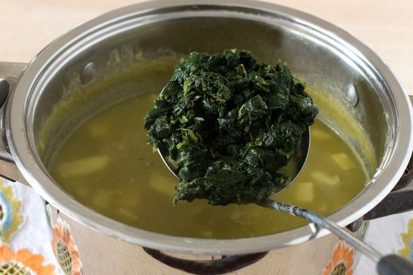 Замороженный шпинат в металлической ложке над кастрюлей с супом