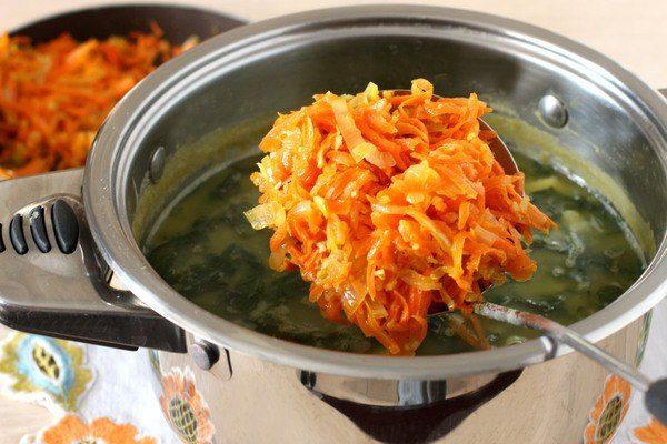 Овощная зажарка в большой ложке над кастрюлей с супом