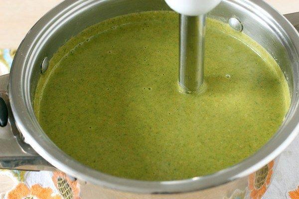 Гороховый суп-пюре со шпинатом в металлической кастрюле с погружным блендером