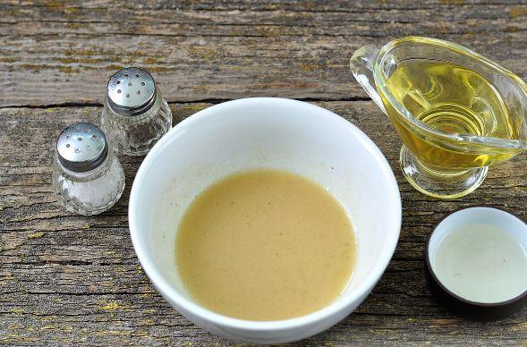 Салатная заправка из горчицы, растительного масла и уксуса в маленькой ёмкости а столе