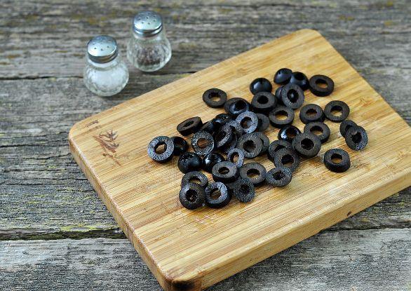 Нарезанные колечками маслины без косточек на деревянной разделочной доске