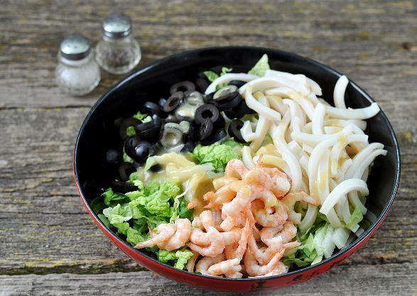 Подготовленные продукты для салата с кальмарами в большой миске на столе