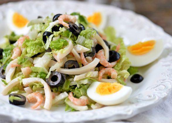 Салат с кальмарами, маслинами и отварным яйцом на красивой белой тарелке