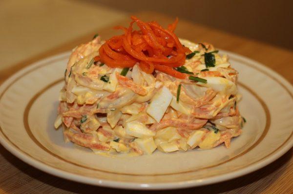 Порция салата из кальмаров и корейской моркови на тарелке