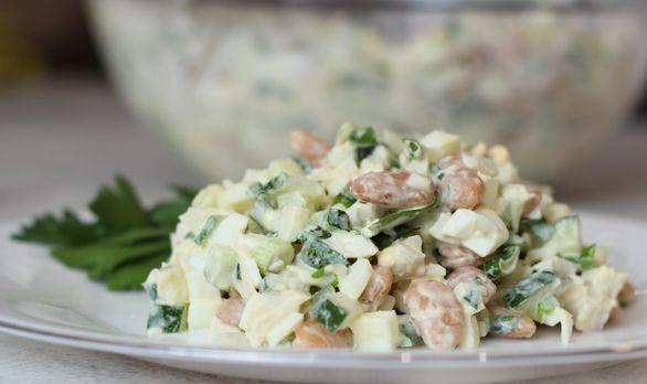 Салат с консервированными кальмарами, фасолью и огурцом на тарелке