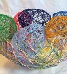 Пасхальные яйца из ниток в корзине из ниток
