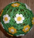 Шар из ниток, украшенный вязаными цветами