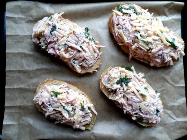 Заготовки для горячих бутербродов с сыром и колбасой в противне с пекарской бумагой
