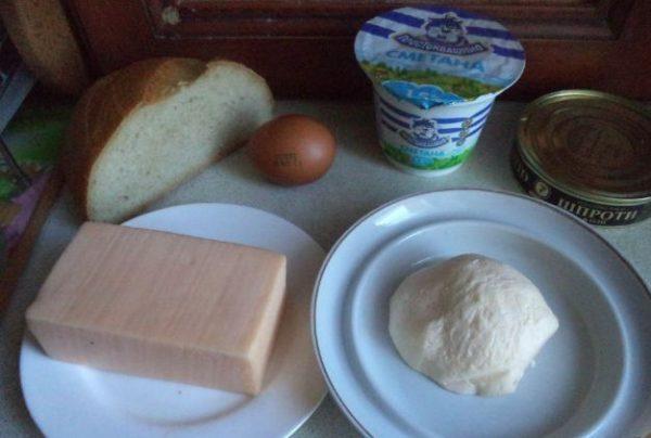 Продукты для приготовления горячих бутербродов со шпротами и сыром на столе