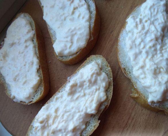 Ломтики батона, намазанные смесью сыра и сметаны