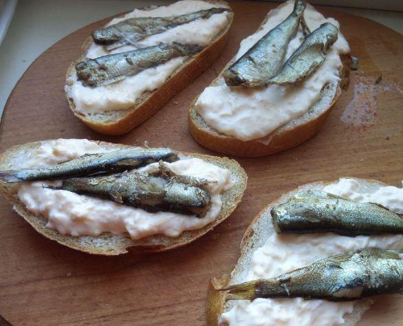 Заготовки для горячих бутербродов с сыром и шпротами на деревянной разделочной доске