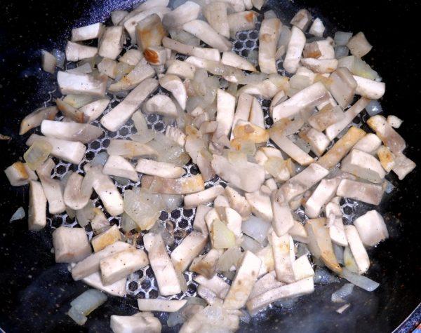 Нарезанные шампиньоны и репчатый лук в сковороде с маслом