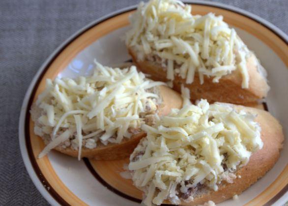 Кусочки багета с рыбно-яичной смесью и тёртым сыром на тарелке