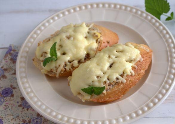 Горячие бутерброды с консервированной рыбой, яйцами и сыром на тарелке