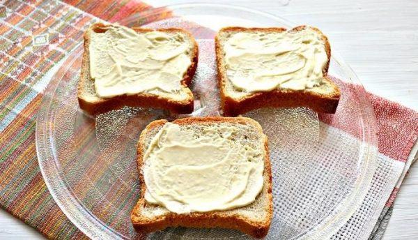 Смазанный майонезом хлеб для тостов на стеклянной тарелке
