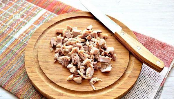 Нарезанное маленькими кусочками отварное куриное мясо на деревянной разделочной доске с ножом