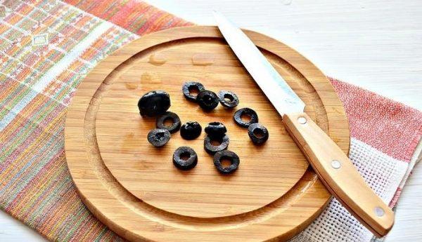 Нарезанные колечками маслина на деревянной разделочной доске с ножом