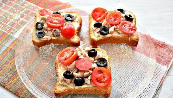 Заготовки для горячих бутербродов с курицей, помидорами и маслинами на стеклянной тарелке