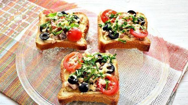 Горячие бутерброды с курицей, помидорами, сыром, оливками и зеленью на стеклянной тарелке