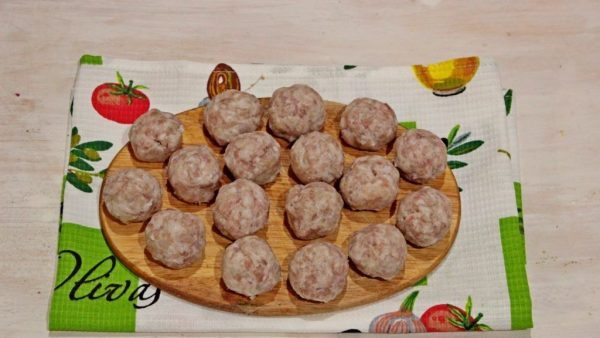 Сырые мясные фрикадельки на деревянной разделочной доске