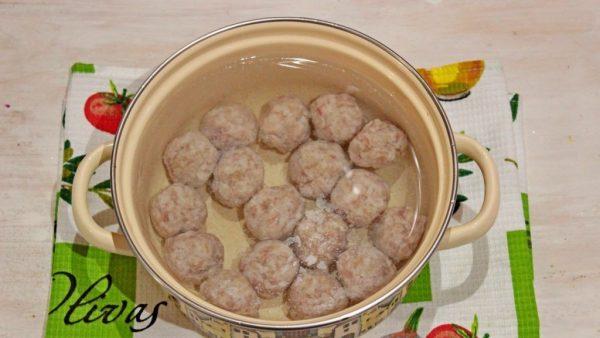 Мясные фрикадельки в кастрюле с водой на кухонном полотенце