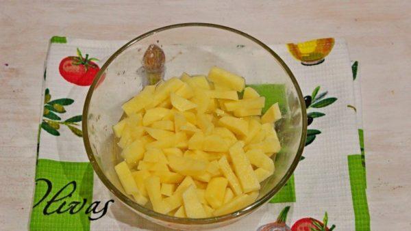 Нарезанный брусочками сырой картофель в стеклянной миске