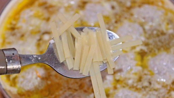 Металлическая ложка с сухой лапшой над кастрюлей с супом