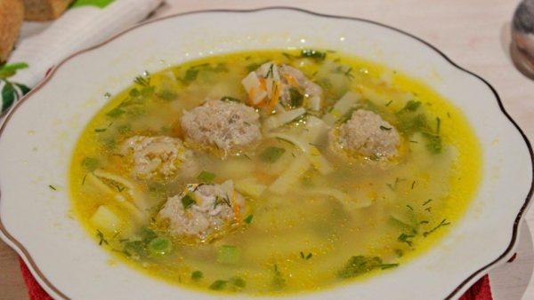 Суп с фрикадельками и лапшой в порционной тарелке на столе
