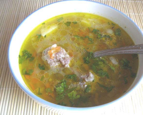 Суп с фрикадельками и рисом в порционной тарелке с металлической ложкой