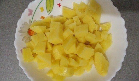 Нарезанный кубиками сырой картофель в тарелке с узором