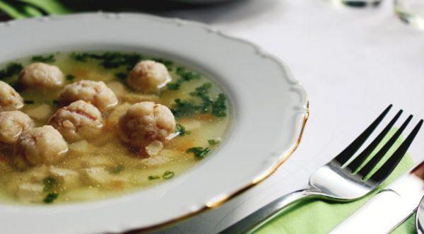 Суп с фрикадельками и зелёным луком в порционной тарелке