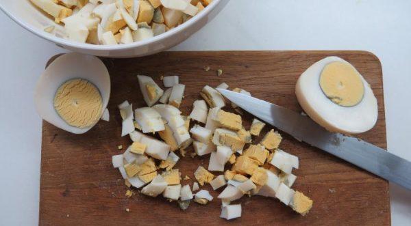 Рубленые варёные яйца на деревянной разделочной доске с ножом