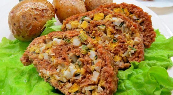 Нарезанный порционными кусочками мясной рулет с яично-луковой начинкой на тарелке с гарниром из картофеля и листьев салата