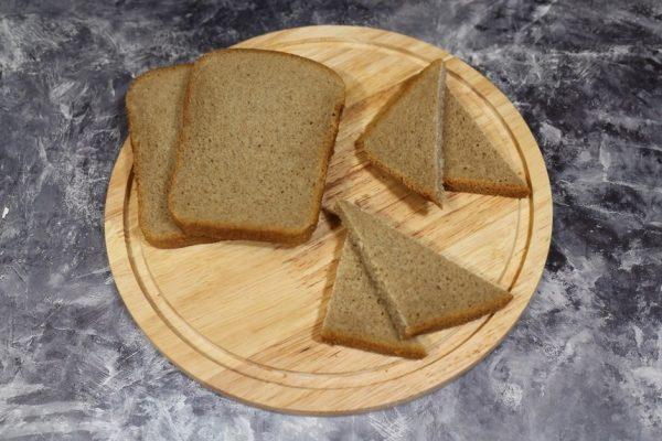 Ломтики ржаного хлеба на круглой разделочной доске из дерева