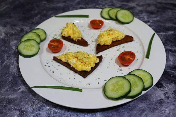 Еврейская закуска с чёрным хлебом на украшенной овощами и зеленью белой тарелке