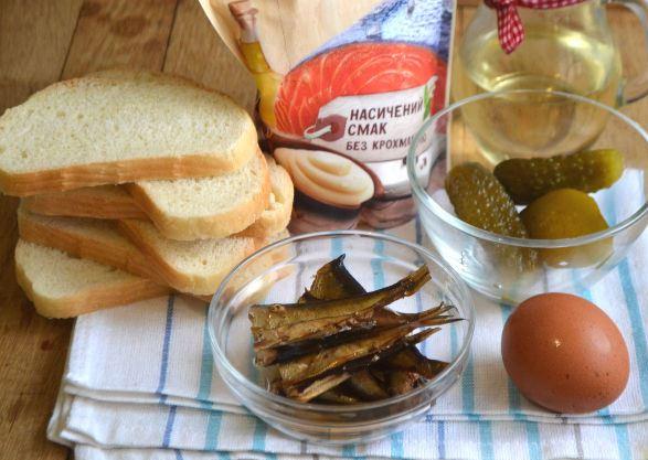 Продукты для приготовления бутербродов со шпротами, яйцом и маринованными огурцами на столе
