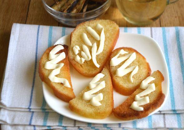 Обжаренные ломтики белого хлеба с майонезом на тарелке