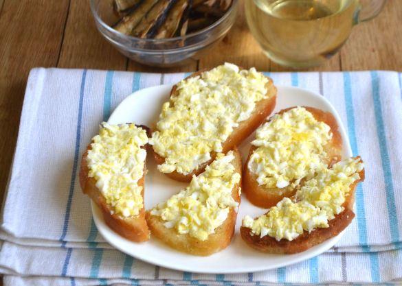 Обжаренные кусочки белого хлеба с майонезом и тёртыми яйцами на тарелке
