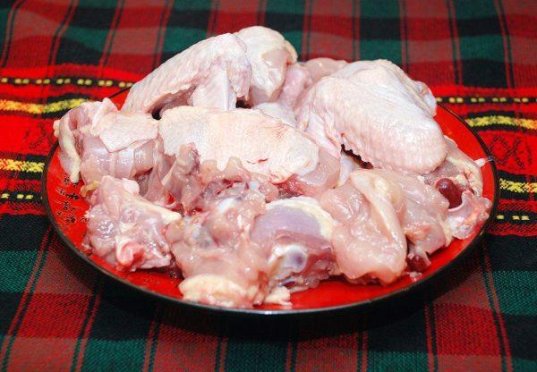 Порезанная на кусочки сырая курица на тарелке