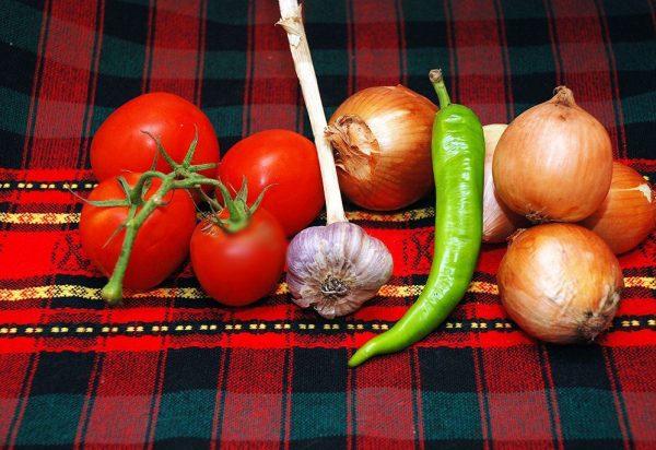 Помидоры, репчатый лук, чеснок и стручок острого перца на столе