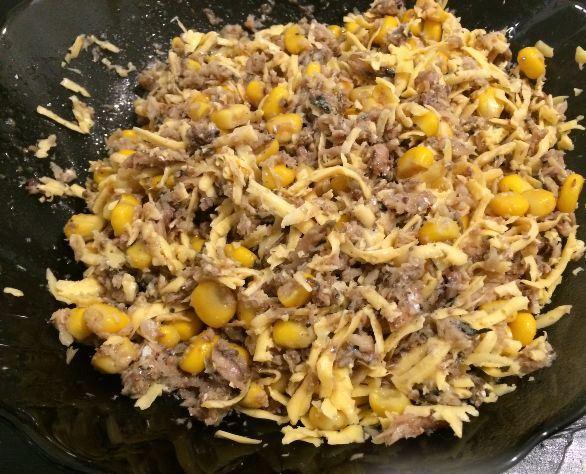 Измельчённые шпроты, консервированная кукуруза и тёртый сыр в стеклянной миске