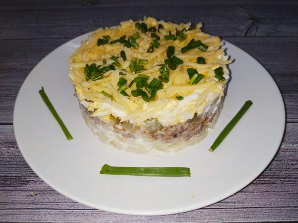 Слоёный салат из шпрот на большой тарелке