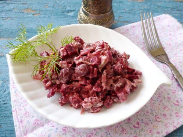 Салат из шпрот, свёклы и консервированной фасоли со свежим укропом на тарелке