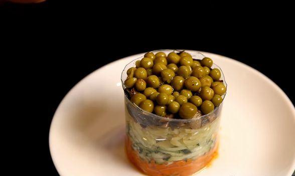 Слоёный салат из шпрот в форме из пластиковой бутылки на белой тарелке