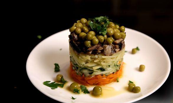 Готовый слоёный салат из шпрот на тарелке с зеленью петрушки