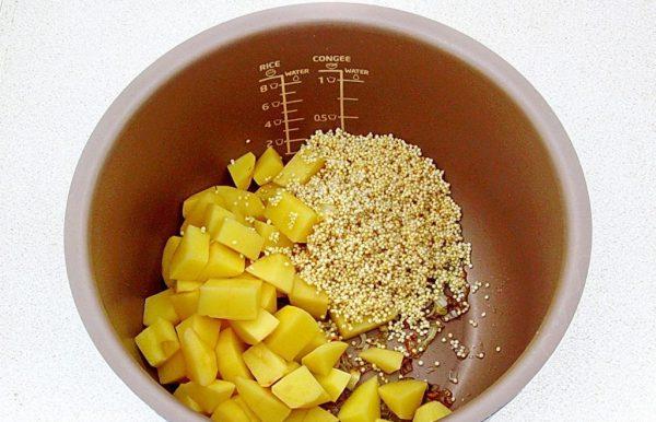 Нарезанный кубиками сырой картофель, пшено и обжаренный репчатый лук в чаше мультиварки