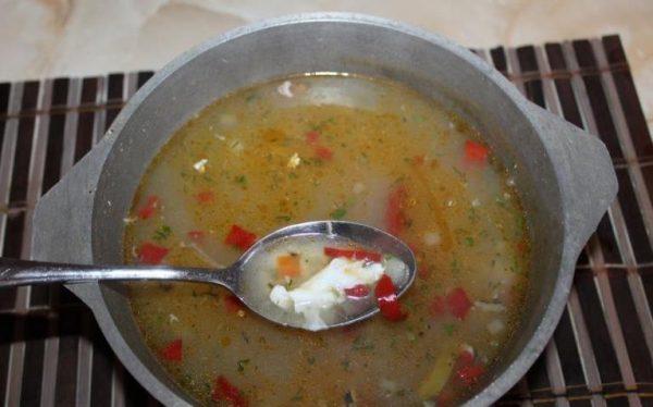 Кастрюля с супом и металлическая ложка с кусочком варёного яичного белка
