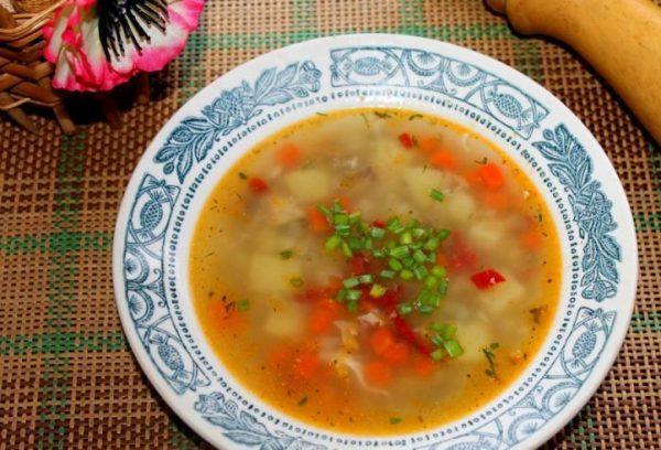 Рыбный суп с овощами и зеленью в красивой порционной тарелке на столе