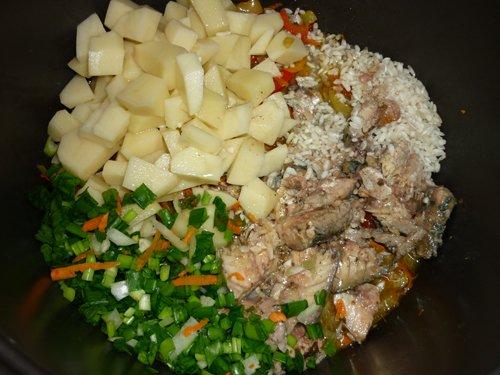 Сырой картофель, зелёный лук, сырой рис и консервированная рыба в чаше мультиварки с обжаренными овощами